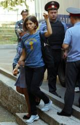 Nadezhda Tolokonnikova, left, a member of feminist punk group Pussy Riot is escorted to a court room in Moscow, Russia, Wednesday, Aug. 8, 2012.