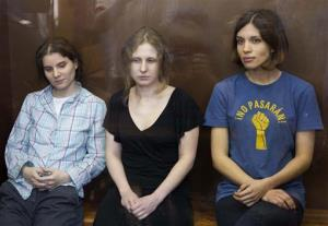 Feminist punk group Pussy Riot members, Nadezhda Tolokonnikova, right, Maria Alekhina, center, and Yekaterina Samutsevich sit in a glass cage at a court room in Moscow, Russia, Friday, Aug. 17, 2012.