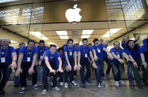 In this Friday, March 16, 2012, photo, Apple employees welcome hundreds of customers in front of the Apple store at a shopping mall in Oberhausen, western Germany.
