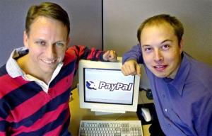 In this Oct. 20, 2000 file photo, PayPal Chief Executive Officer Peter Thiel, left, and founder Elon Musk, right, pose with the PayPal logo at corporate headquarters in Palo Alto, Calif.