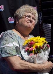 In this June 28, 2012 file photo, bus monitor Karen Klein, of Greece, NY, holds flowers during an award ceremony in her honor at a radio station in Boston.