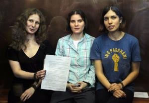 In this Aug. 17 file photo, feminist punk group Pussy Riot members show the court's verdict as they sit in a glass cage at a courtroom in Moscow.
