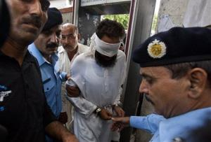 Pakistani police officers escort blindfolded Muslim cleric Khalid Chishti to appear in court in Islamabad, Pakistan, Sunday, Sept. 2, 2012.