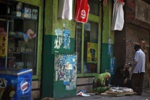An Egyptian street vendor sleeps as another sells bread on the side of a street in Cairo.