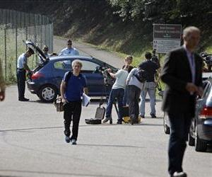 Journalists wait in front of Gendarmes, who block access to the site of a killing near Chevaline, French Alps, Sept. 6, 2012.