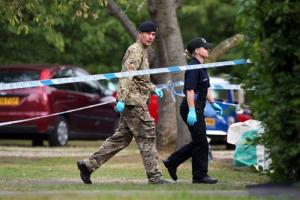 A member of the Royal Logistic Corps bomb disposal team walks with a police officer close to the home of Saad al-Hilli, in Claygate, England, Sept. 10, 2012.