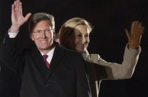Former German President Christian Wulff, left, and his wife Bettina wave to guests after the Grossen Zapfenstreich ceremony, which was held to mark his departure from office, in Berlin, March 8, 2012.