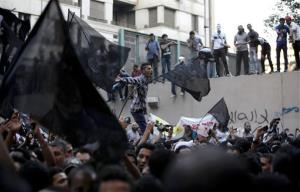 Egyptian protesters climb the walls of the U.S. Embassy in Cairo.