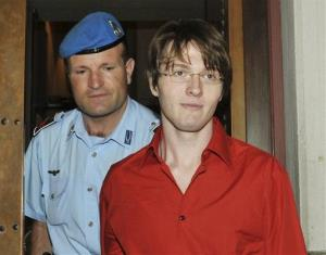 Raffaele Sollecito is escorted by a penitentiary police officer as he arrives for a hearing in the Meredith Kercher murder trial, in Perugia, Italy, in 2009.