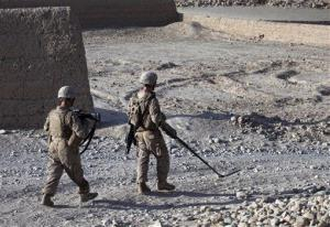 In this Sept. 5, 2011 photo, US Marines patrol with the help of a metal detector, in Sangin district, Helmand province. Marines are heading to US embassies in Libya to increase security.