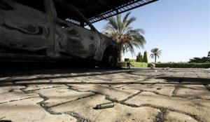 A bullet casing is seen on the ground near one of the burnt-out cars of the US consulate in Benghazi.