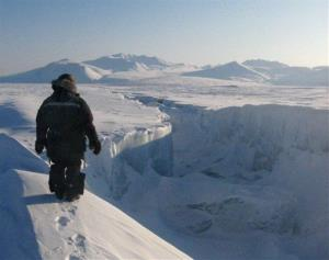 In this 2008 file photo, a Canadian Ranger looks along the length of one of the gaping new cracks in the Ward Hunt Ice Shelf in the Arctic.
