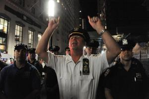 Police order a group of people associated with the Occupy movement to disperse in front of Trinity Church in New York, Saturday, Sept. 15, 2012.