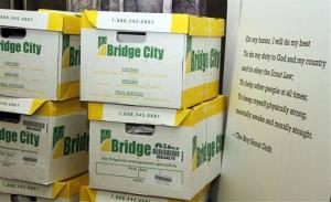 In this June 14, 2012 file photo, boxes full of records from the Boy Scouts of America are seen next to the Boy Scout oath at an attorney's office in Portland, Ore.