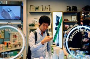 In this Thursday, Aug. 23, 2012 photo, Cho Won-Hyuk, a 24-year-old college student, shops for skincare and makeup products at a cosmetics store in Seoul, South Korea.