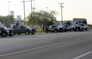 Mexican federal police cluster in front of the prison in Piedras Negras, Mexico, yesterday following a prison break of some 132 inmates.