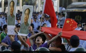 A Chinese man shouts anti-Japan slogans with Chinese national flags near portraits of the late Communist leader Mao Zedong in front of the Japanese Embassy in Beijing Tuesday, Sept. 18, 2012.