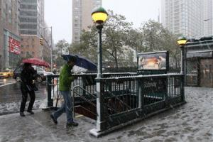 People enter a subway station in New York as it snows Saturday, Oct. 29, 2011.