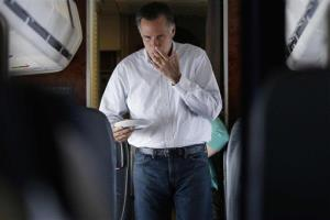 Mitt Romney licks his fingers as he walks back to his seat after making himself a peanut butter and honey sandwich on his campaign plane en route to Las Vegas, Friday, Sept. 21, 2012.