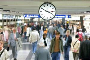 In this Sept. 29, 2005 file photo commuters walk under a Swiss railroad station clock at the Zurich main station.