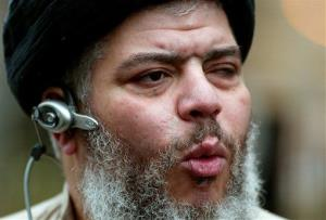 In this Jan. 23, 2004, file photo, self-styled cleric Abu Hamza al-Masri leads his followers in prayer in London.