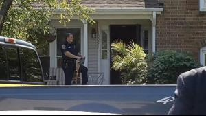 A police officer exits the Fairfax County house where a family of four was found dead.
