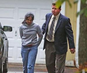Annie Dookhan, center, is escorted to a cruiser outside her home in Franklin, Mass., Friday, Sept. 28, 2012.