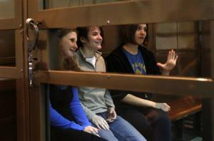 Pussy Riot members, from left, Maria Alekhina, Yekaterina Samutsevich, and Nadezhda Tolokonnikova, sit in a glass cage at a court room in Moscow, Russia on Monday Oct. 1, 2012.