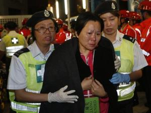 A survivor supported by rescuers, is taken onto shore after a collision involving two vessels in Hong Kong Tuesday, Oct. 2, 2012.