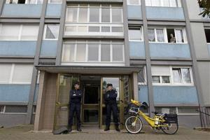 French police officers stand guard at the entrance of a building in Strasbourg, France, Saturday Oct. 6, 2012.