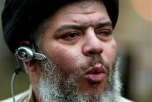 In this Jan. 23, 2004 file photo, self-styled cleric Abu Hamza al-Masri leads his followers in prayer on a street outside Finsbury Park Mosque.