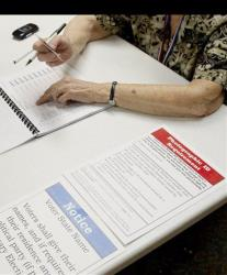 A poll worker checks the identification of a voter in Lawrence, Kan., Tuesday, Aug. 7, 2012.