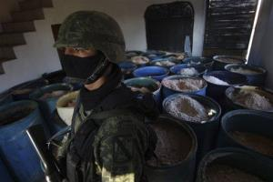FILE - In this Feb. 9, 2012, file photo a soldier stands in a room full of barrels containing white and yellow powder after a seizure of 15 tons of pure methamphetamine at a small ranch in Tlajomulco de Zuniga, on the outskirts of Guadalajara, Mexico. Mexican drug cartels are...