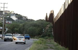 In this photo taken Aug. 9, 2012, vehicles drive along the border fence in Nogales, Mexico.
