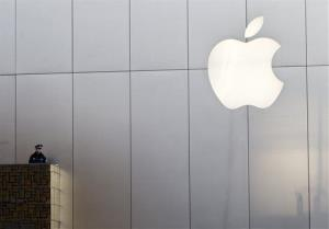 A police officer stands watch near Apple's logo at a store in Beijing Friday, Jan. 13, 2012.