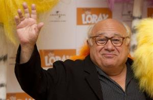 Danny DeVito waves as he stands next to a fluffy Lorax, during a photocall for the film, The Lorax, at the Dorchester hotel in central London, Monday, March 12, 2012.