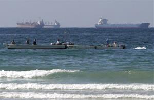 Fishing boats are seen in front of oil tankers on Persian Gulf waters, south of the Strait of Hormuz.