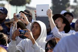 Spectators photograph the space shuttle Endeavour as it slowly moves down Martin Luther King Blvd. in Los Angeles Sunday, Oct. 14, 2012.