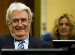 Radovan Karadzic smiles as he takes his seat on the defense bench in a courtroom to start his defense at the UN war crimes tribunal in The Hague, Netherlands, Oct. 16, 2012.