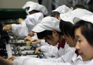 In this Wednesday, May 26, 2010, file photo, staff members work on the production line at the Foxconn complex in Shenzhen, China.