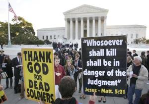 Westboro Baptist Church member Jacob Phelps of Topeka, Kan., holds signs as people engage him in front of the Supreme Court in Washington in 2010.