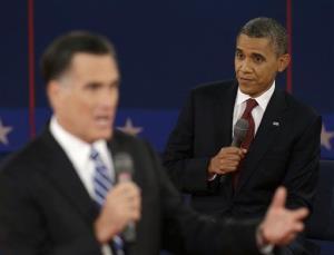 President Obama listens as Mitt Romney speaks.