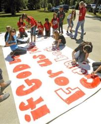 In this Sept. 19 file photo, Kountze High School cheerleaders and other children work on a large sign in Kountze, Texas.