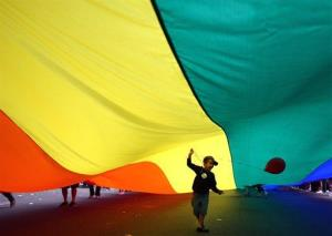 A child holds a balloon under a Pride flag in Seattle.