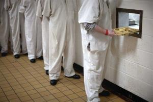 Prisoners are handed lunch through a hole in the cafeteria wall at the state prison Thursday, March 3, 2011 in Jackson, Ga.