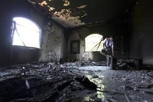 In this Sept. 13, 2012 file photo, a Libyan man investigates the inside of the  US Consulate, after an attack that killed four Americans, including Ambassador Chris Stevens.