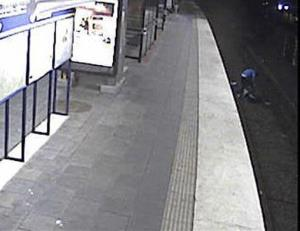 Image from CCTV footage file photo dated Sept. 8, 2012, shows a man being robbed while on subway tracks.