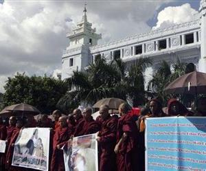 Buddhist monks hold signs during a rally against recent violence in Rakhine state, outside the city hall in Yangon, Oct. 25, 2012.