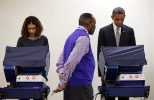 President Obama casts his vote at the Martin Luther King Community Center in Chicago. Elections official Eli Selph, center, isn't peeking. He's standing nearby to answer voters' questions.