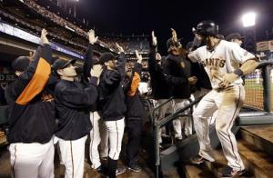 San Francisco Giants' Marco Scutaro is congratulated in the dugout after scoring on a sacrifice fly by Hunter Pence during the eighth inning.